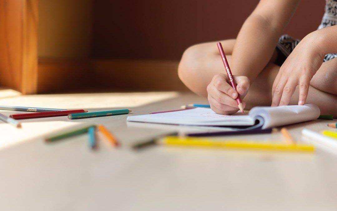 Un enfant dessine sur un cahier